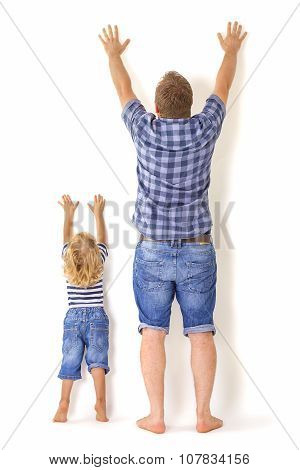 Growing Up Concept. Father And Son Standing with Their Backs to the Camera