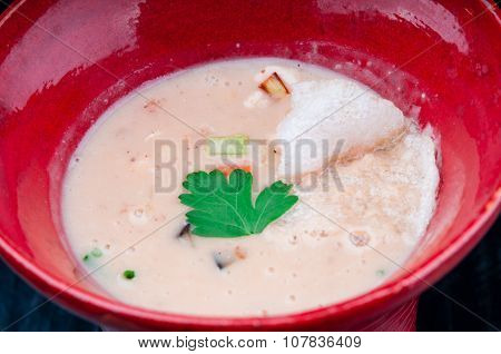 Vegetable soup served in a red cup on a black wooden table