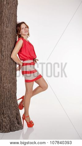 Young Woman Is Leaning Against A Tree