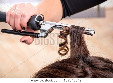 Hairstylist Using A Curling Iron Or Tongs