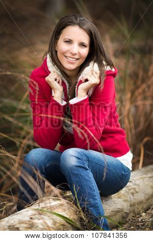 Beautiful smiling woman sitting on log