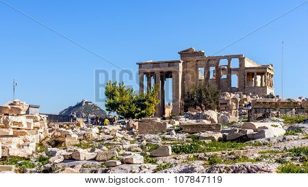 Tourists take photos of the Old Temple of Athena