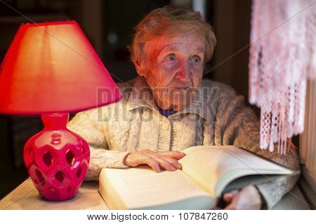 Elderly woman reads a book with a table lamp.