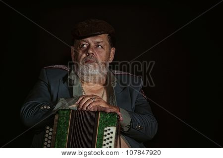 Portrait of an old retired military man with acordian looking with hope