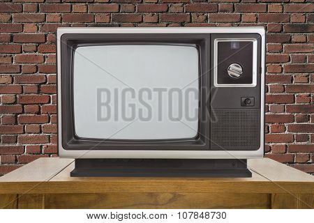 Old portable television and table with brick wall.