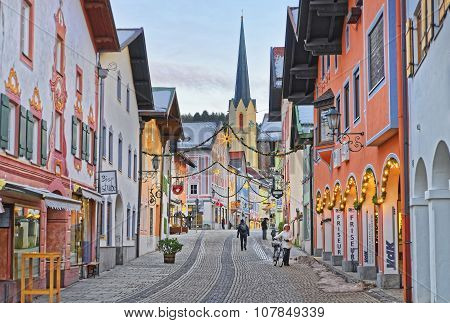 GARMISCH-PARTENKIRCHEN GERMANY - JANUARY 06 2015: Cozy narrow street of Garmisch-Partenkirchen (Germany) with the steeple of Maria-Himmelfahrt (Assumption day) church visible in the background. Selective focus.