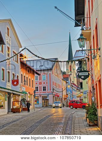 GARMISCH-PARTENKIRCHEN GERMANY - JANUARY 06 2015: Cozy narrow street of Garmisch-Partenkirchen with Christmas illumination. Maria-Himmelfahrt (Assumption day) church visible in the background