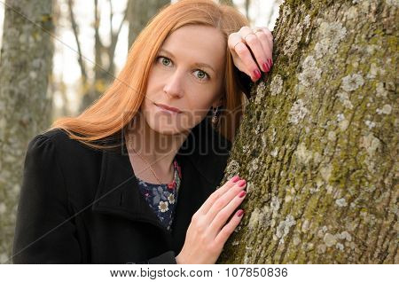 Outdoor Portrait Of Red Haired Woman With Green Eyes. A Young Woman Stands Near Tree