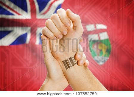 Barcode Id Number On Wrist With Canadian Province Flag On Background - Manitoba