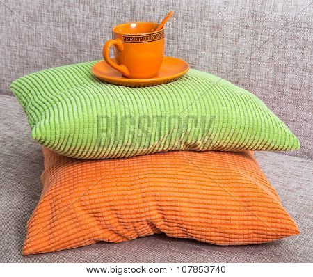 Ceramic Orange Cup With A Saucer On A Pile From Green And Orange Pillows On A Gray Sofa