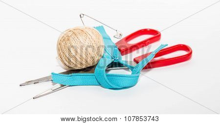 Blue Zipper, Red Scissors And Ball Of Beige Threads With A Pin