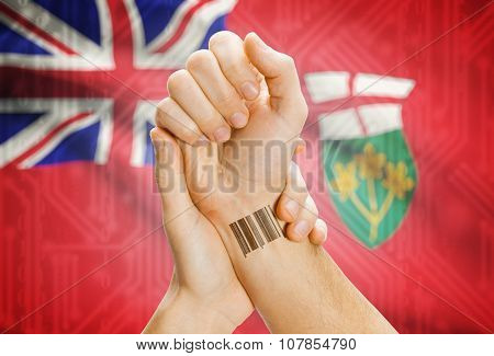 Barcode Id Number On Wrist With Canadian Province Flag On Background - Ontario