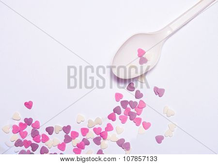 Heart candies on white spoon