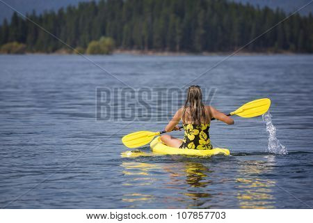 Beautiful fit and active woman paddling her kayak on a scenic, peaceful mountain lake