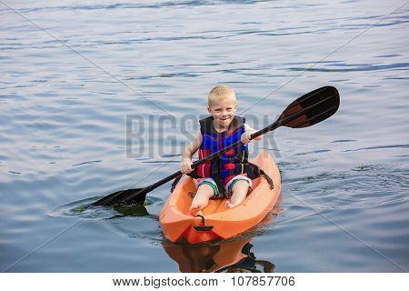 Young Boy paddling a kayak on a beautiful lake