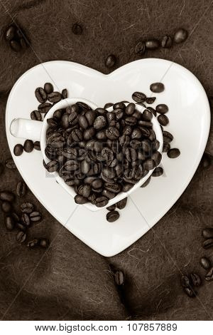 Heart Shaped Cup With Coffee Beans On Brown