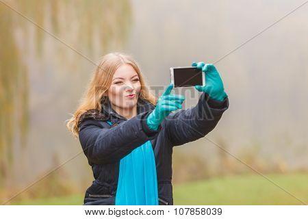 Happy Woman In Autumn Park Taking Selfie Photo.