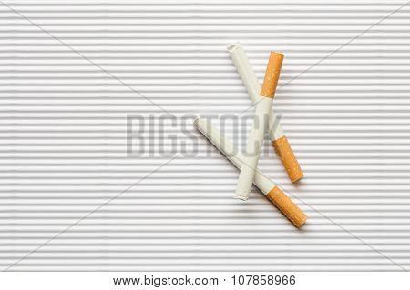 Cigarette On White Paperboard Background, Overhead View Of Cigarette