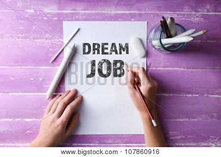 Dream job concept. Hands with color pencils and sheet of paper on wooden table