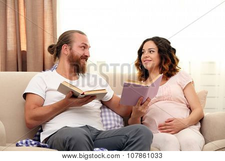 Happy beloved couple reading books in waiting for baby's birth on sofa in the room
