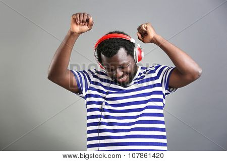 African American man with headphones on grey background