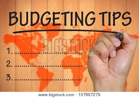 Hand Writing Budgeting Tips Over Blur World Background