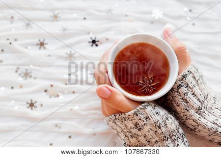 Woman Holds A Cup Of Hot Tea With Anise Star. Winter Fabric Background With Sparkling Snowflakes