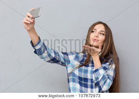 Beautiful happy girl with long hair in checkered shirt making selfie using cellphone sending an air kiss