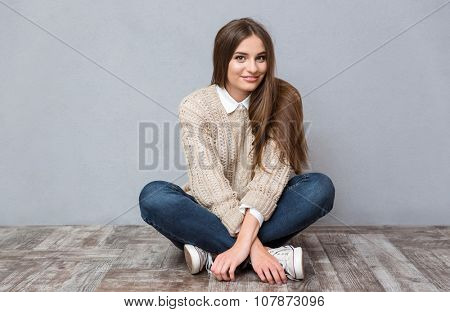 Beautiful smiling girl with long hair in beige sweater and jeans sitting on wooden floor with legs crossed