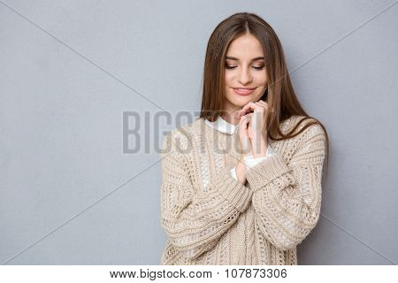 Portrait of beautiful young sweet shy pretty girl in beige sweater looking down