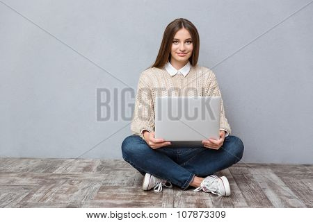 Young confident hapy smiling woman using laptop sittin on wooden floor