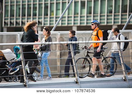 LONDON, UK - SEPTEMBER 9, 2015: Lots of people crossing bridge on the way to work. Canary Wharf busi