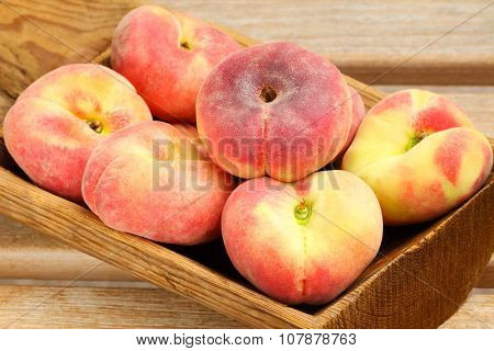 A wooden bowl full of Saturn Peaches, known as flat Donut peach