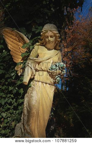 Majestic View Of Statue Of Golden Angel Illuminated By Sunlight Against A Background Of Dark Foliage