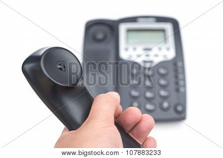 Man Holding A Black Telephone Receiver On A White Background