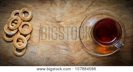 Cup Of Tea, Bagels Dry On The Old Rustic Table Wood Background.