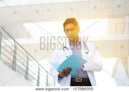 Portrait of Asian Indian medical doctor reading on medical report, standing outside hospital building, beautiful golden sunlight at background.