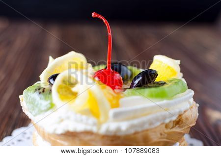 Choux Pastry With Fruit On A Wooden Background Close-up