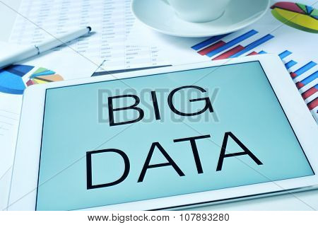 the text big data in the screen of a tablet on a table full of charts and spreadsheet, and with a cup of coffee or tea