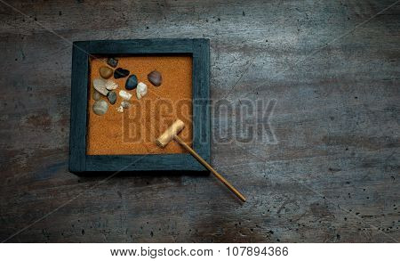 Zen Garden With Rake And Stones On Orange Sand