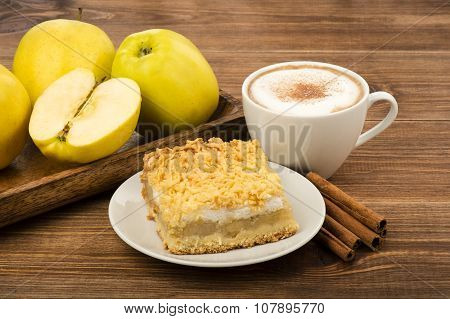 A piece of apple pie with cup of coffee and cinnamon sticks on the wooden background.