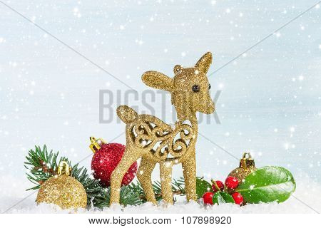 Fawn with fir branch and holly leaves in the snow.  Christmas background.