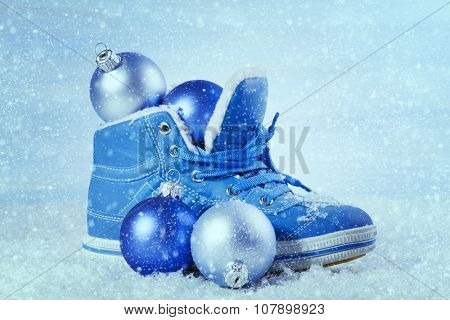 Blue shoe with Christmas decorations in the snow. Christmas background