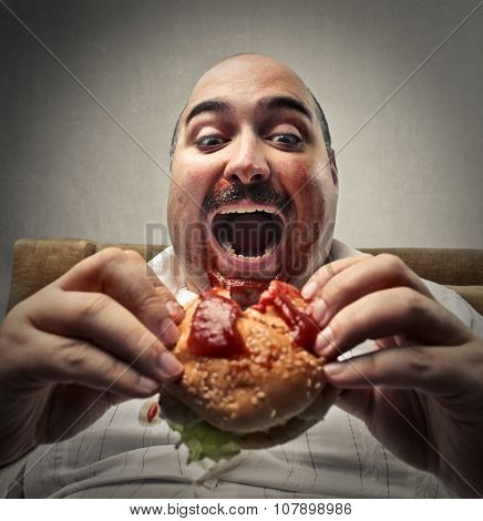 Hungry man eating a hamburger