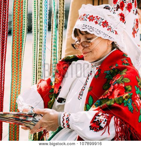 Woman in national Belarusian folk costume weaving belt. Belarus