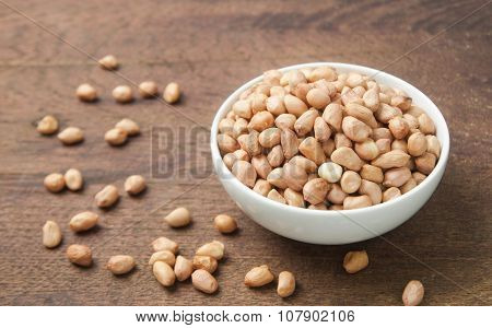 Raw peanuts in white bowl on wooden table.