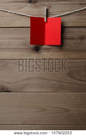 Red Blank Greetings Card Pegged To String On Wood Background