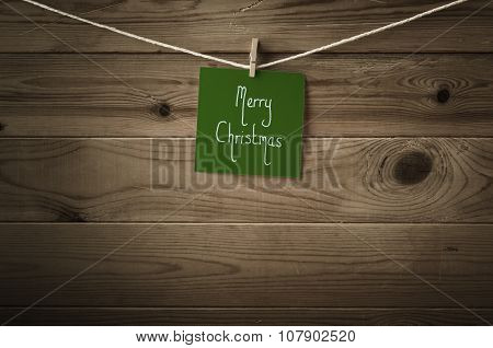 Green Merry Christmas Message Pegged To String Against Wood Planks