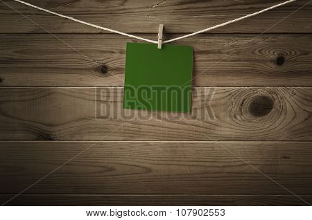 Blank Green Message Pegged To String Against Wood Planks
