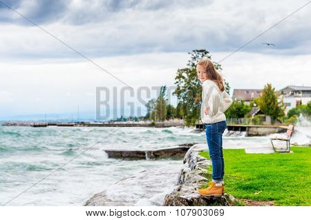 Cute little girl of 8 years old playing by the lake on a very windy day, wearing warm white knitted